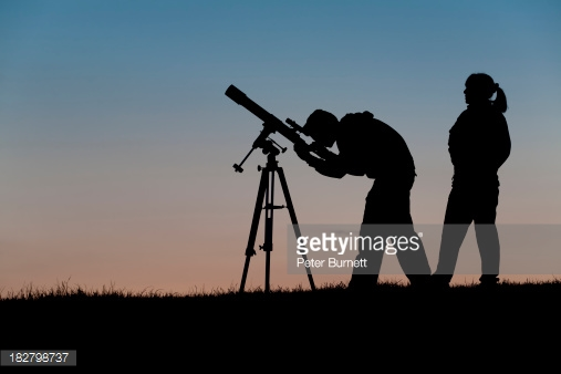Two young amateur astronomers observing the night sky using a three inch refracting telescope on an equatorial mount.